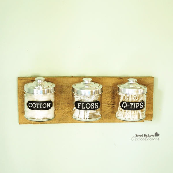 Three glass jars stuck to a wooden plank on a bathroom wall.