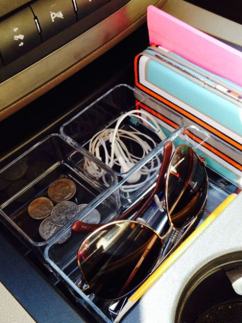 Acrylic trays inside a car filled with coins, headphones and a pair of sunglasses