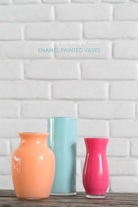 Three enamel painted vases of different colors sat on a dark wood surface.