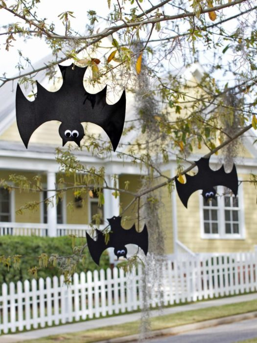 Three paper black bats with googly eyes hanging on a tree outside.