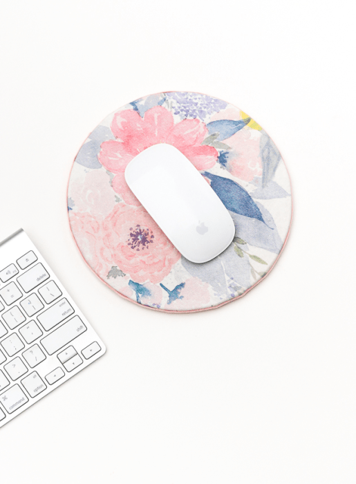 A mouse sat on a mousepad with a homemade floral design.