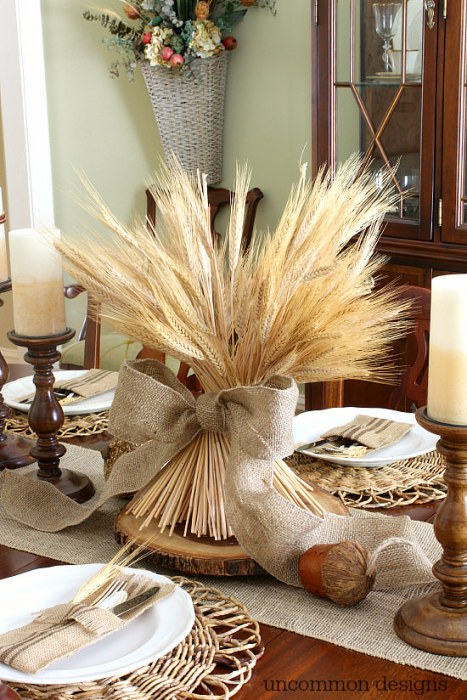 A bundle of wheat wrapped around in a bow sat on a table runner.