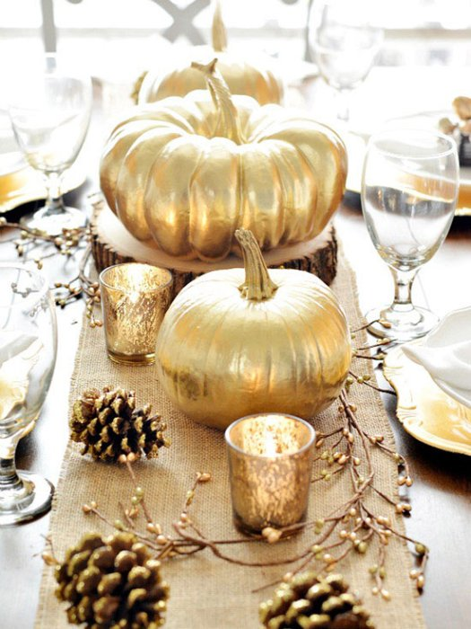A table runner featuring golden pumpkins, candles and pinecones.