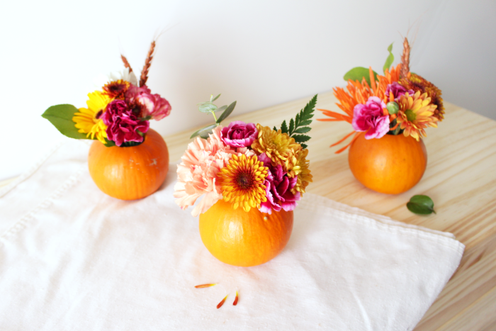 Three hollowed out small pumpkins with floral decorations inside them.
