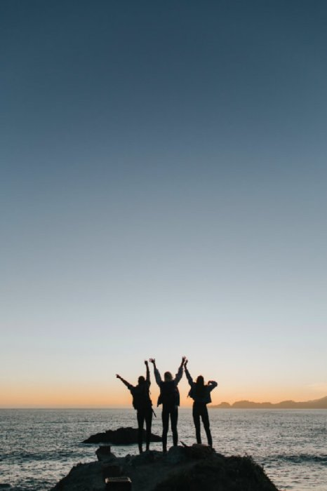 3 women stood near the sea at sunset waving their arms in the air excitedly