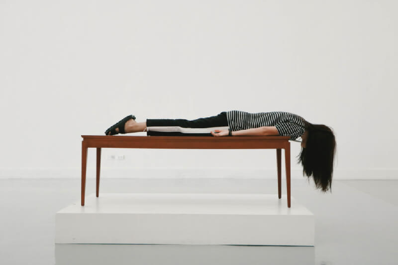 A woman planking on a table inside a museum