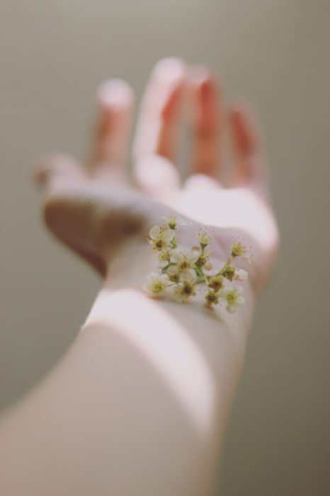 An outstretched forearm with little white flowers resting on it