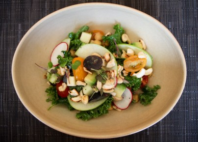 Cartago Salad made with three different types of quinoa, kale, avocado, chickpeas, green apple, grapes, cashews, and a 'tapa de dulce' vinaigrette