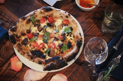 … a pizza topped with eggplant, pine nuts, ricotta, tomatoes and raisins