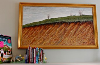 A row of Ruth's books nestle beneath a painting by her late husband Talmadge Moose,