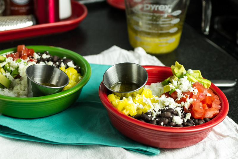 This garlicky black bean rice bowl is packed with all sorts of yummy things...rice, black beans, tomatoes, avocado, pineapple, & feta with a mojo sauce!   recipe from Chattavore.com