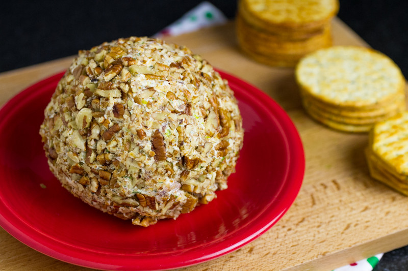 a photograph of a cheddar bacon ranch cheese ball on a cutting board with crackers in the background