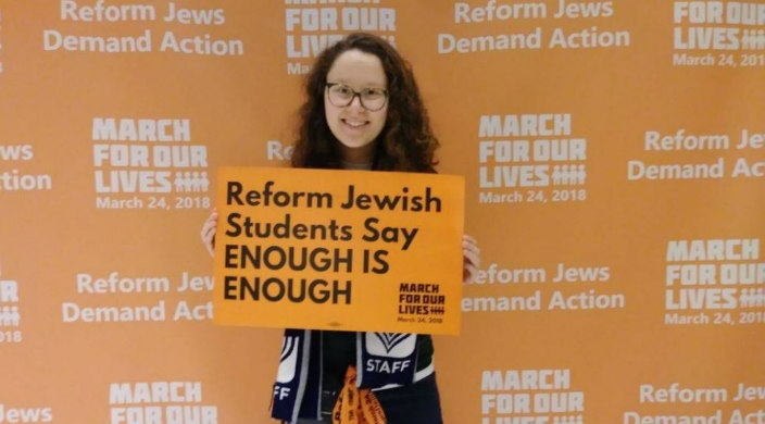 Jewish young adult holding a sign about gun violence prevention in front of a March for Our Lives banner