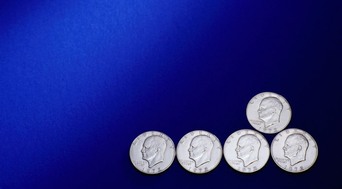 Five shiny silver dollars on a blue background
