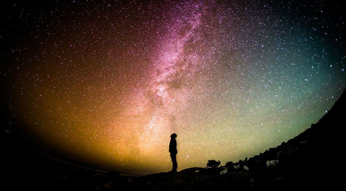 Silhouette of a man staring up at the Milky Way night sky