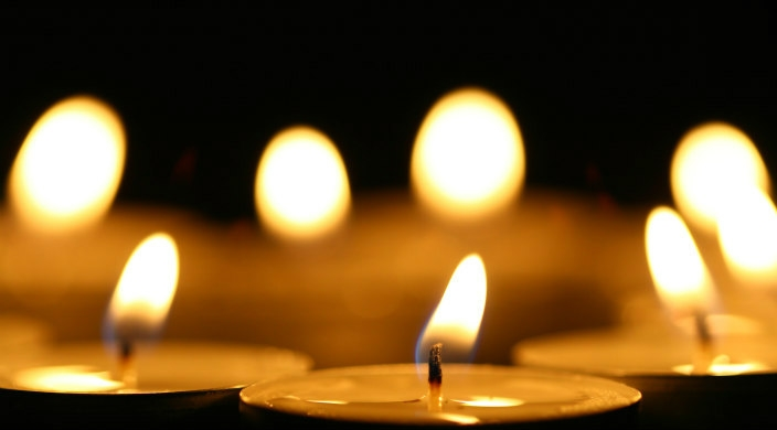 Group of small yellow candles; flames of background candles are slightly out of focus