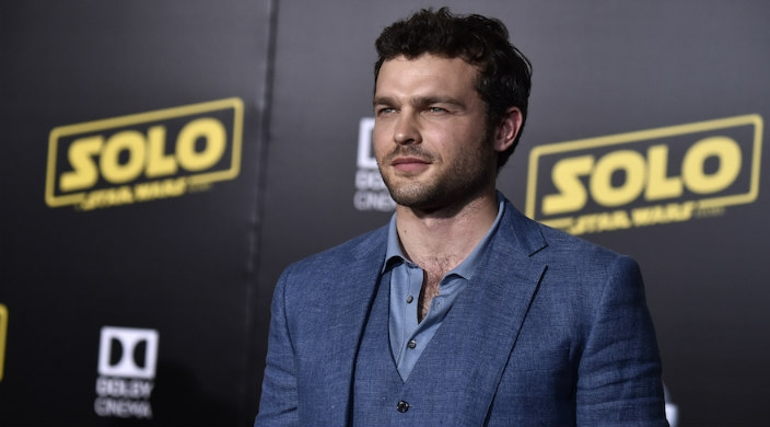 """Alden Ehrenreich standing in front of a step-and-repeat board with the """"Solo: A Star Wars Story"""" logo on it"""