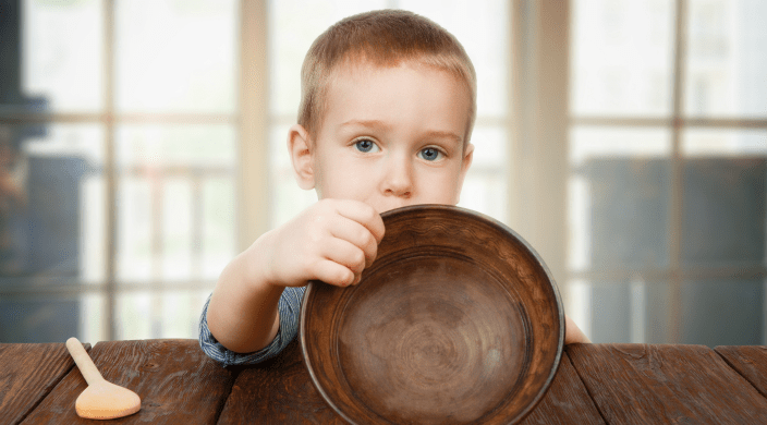 Small boy holding empty bowl signifying hunger