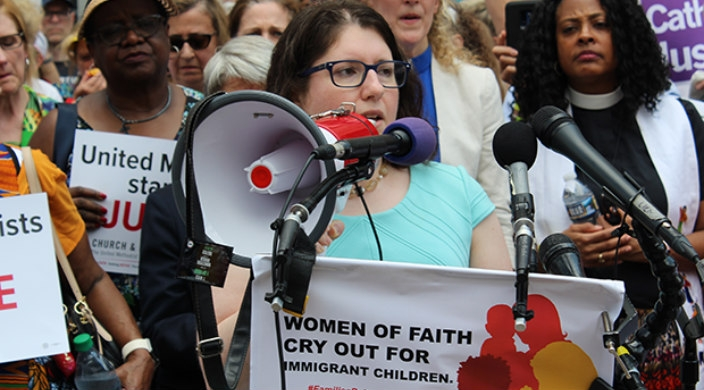 Female speakers in front of a microphone and a podium that reads WOMEN OF FAITH CRY OUT FOR IMMIGRANT CHILDREN