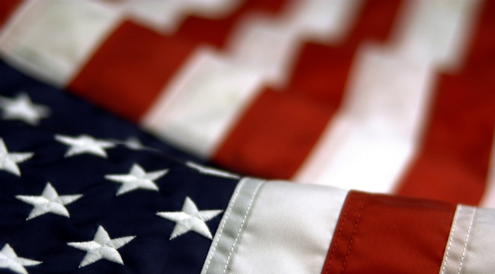 Close up on American flag; stars in the foreground, stripes in the background