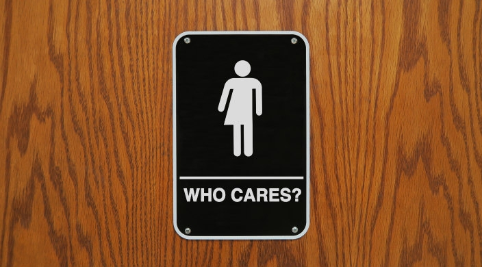 "Gender neutral bathroom sign that says, ""Who Cares?"" with an image that is 1/2 man and 1/2 woman"