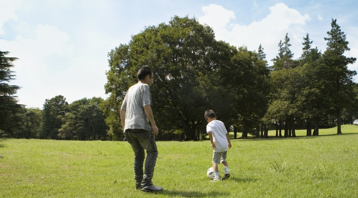 Man and young boy kicking a soccer ball on a grassy field