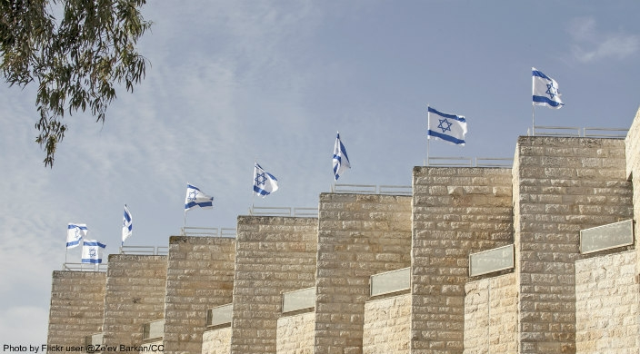 Jerusalem stone columns, each topped by a waving Israeli flag
