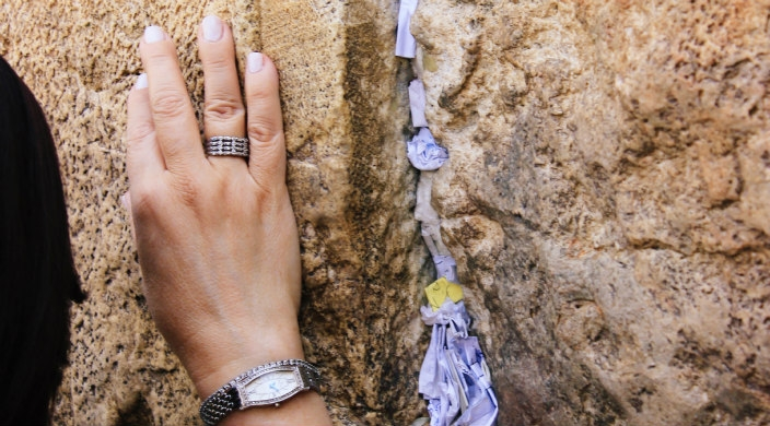Woman's hand on the Western Wall next to notes in a crevice