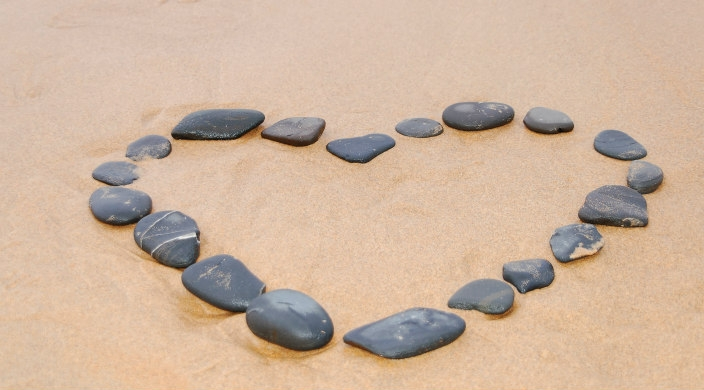 Flat stones laid out to form the shape of a heart on wet beach sand