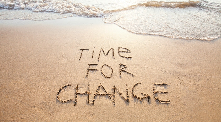Time for change written in the sand with waves coming toward the words