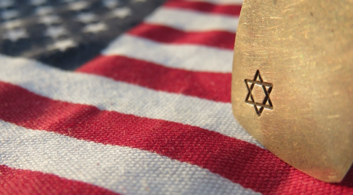American flag with a stone that has a Star of David on it resting across one corner of the flag