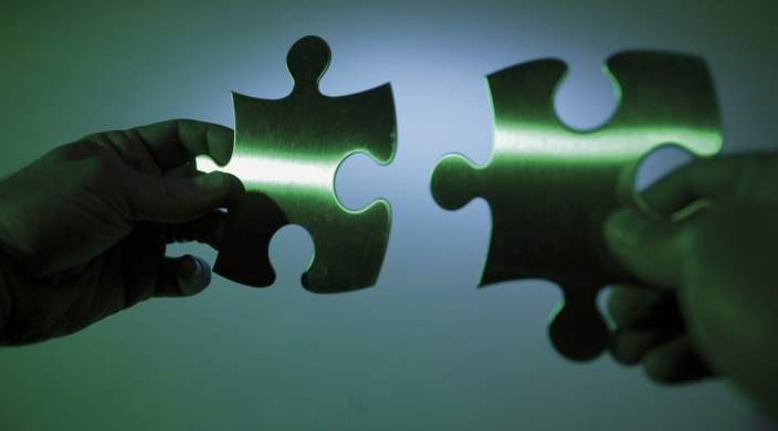 Pair of hands holding two puzzle pieces