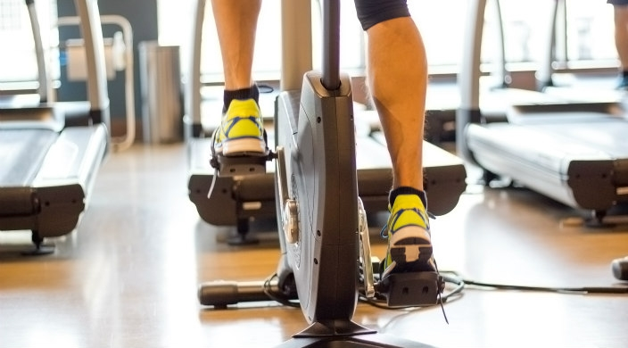 Back of the legs and feet of a person on a stationary bicycle in a gym