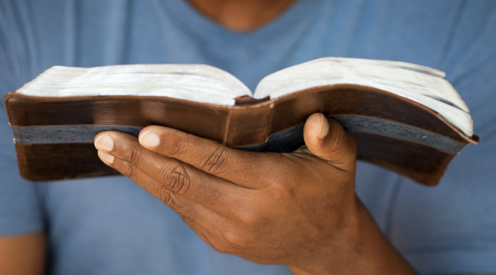 Man holding an open Bible in the palm of his left hand