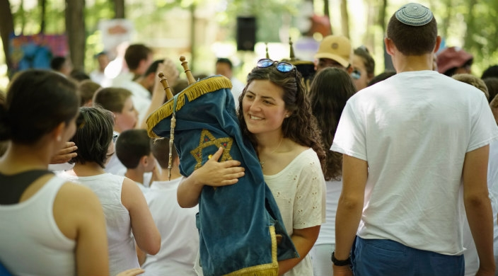 Young woman carrying a Torah scroll through the congregation at camp