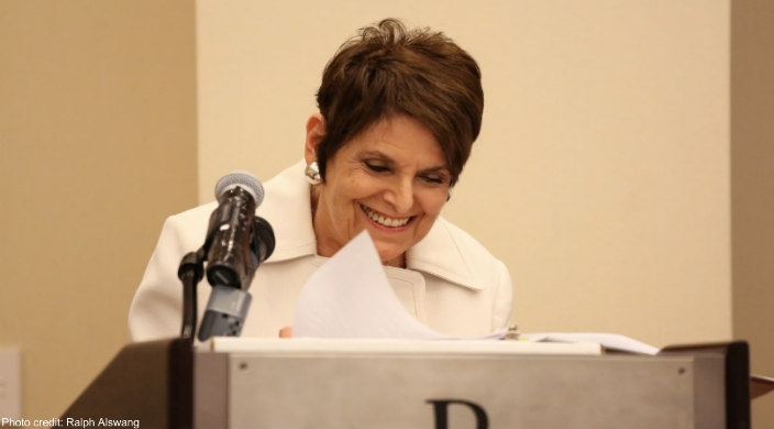 A shorthaired Rabbi Lynne Landsberg speaking at a podium