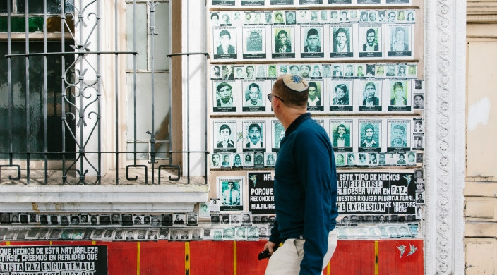 A man in a kippah walks by a wall of photos of people who disappeared during Guatemalas internal armed conflict