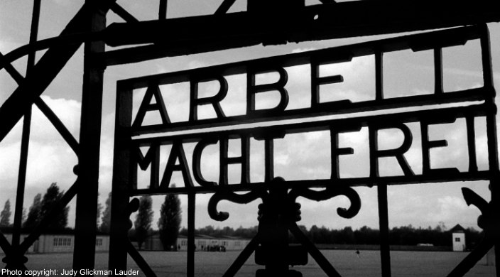 Judy Glickman Lauders black and white photo of Auschwitz gate entrance reading ARBEIT MACHT FREI
