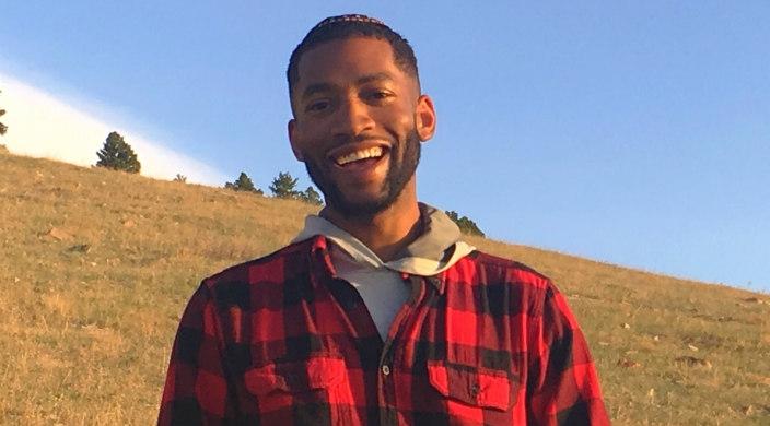 Smiling young man outdoors wearing a kippah and a plaid shirt