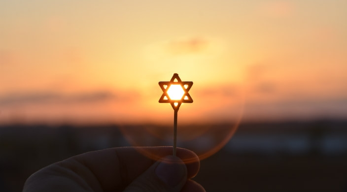 Tiny Star of David charm held up against a sunset