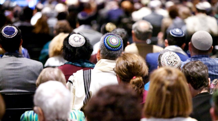 Back view of the heads of worshipers facing forward wearing kippot