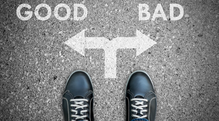 A pair of feet faced with a choice: do good or do bad, which are noted on the ground in front of the feet