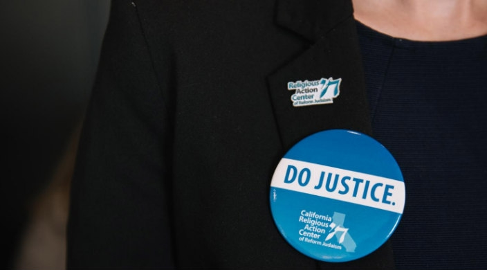 Closeup of the buttons on a persons blazer that read DO JUSTICE and RELIGIOUS ACTION CENTER OF REFORM JUDAISM