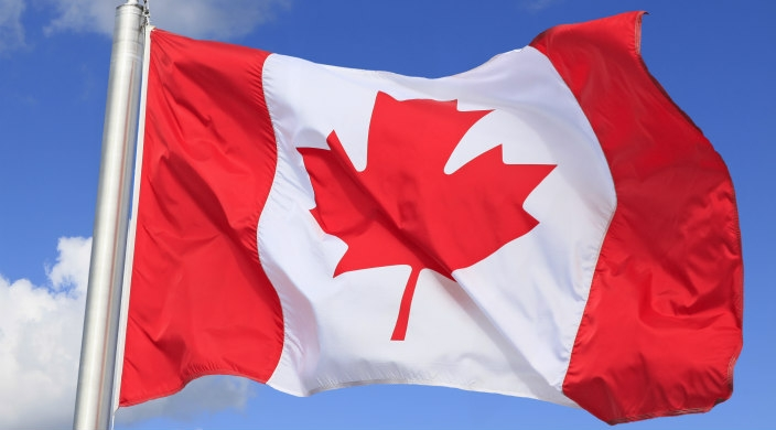 Canadian flag on flagpole with bright blue sky in the background