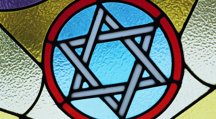 Stained glass window that includes a Jewish start in the middle