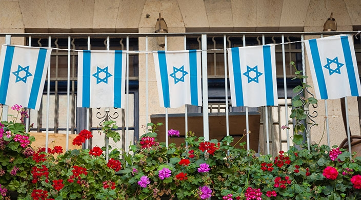 String of Israeli flags, wrought iron fence and blooming flowers