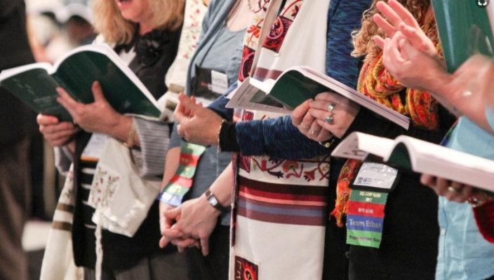 Closeup of a row of people standing with open prayer books and wearing prayer shawls
