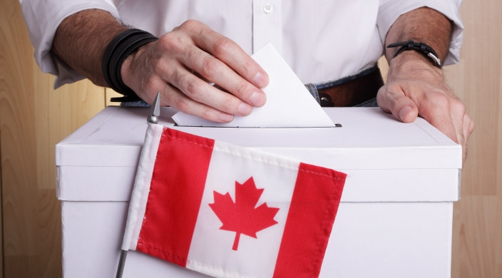 A mans hands dropping a ballet into a ballot box with a Canadian flag in front