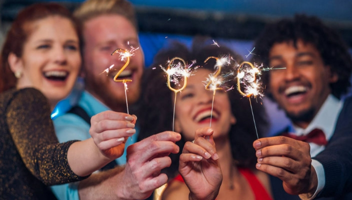 Four smiling people holding 2020 sparklers toward the camera