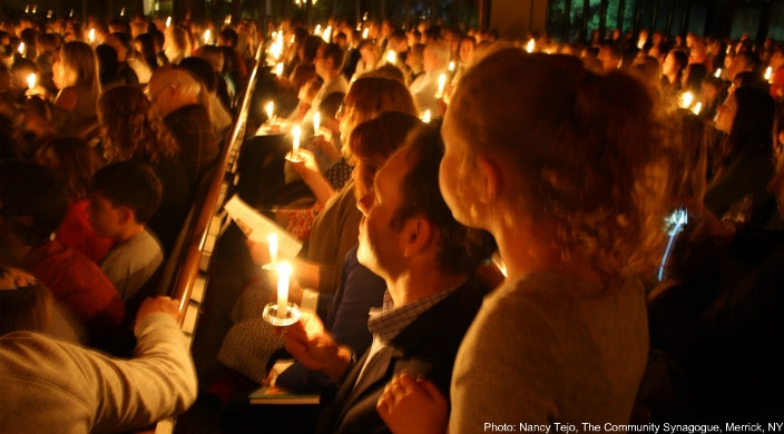 A congregation full of people holding individually lit candles as if in a service of some sort